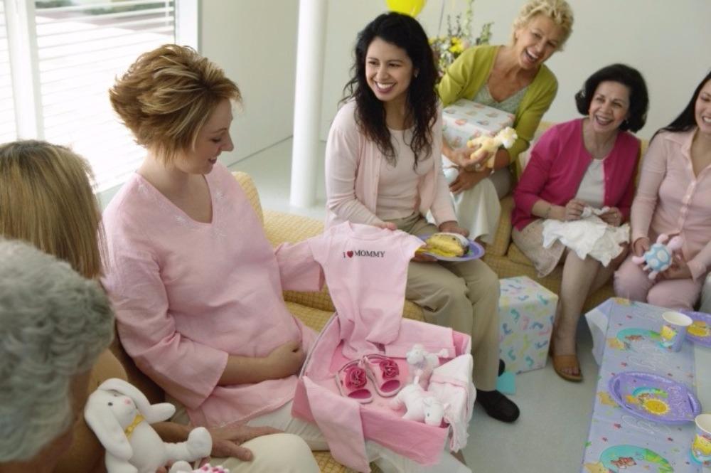 Mãe abrindo um presente com as amigas ao lado
