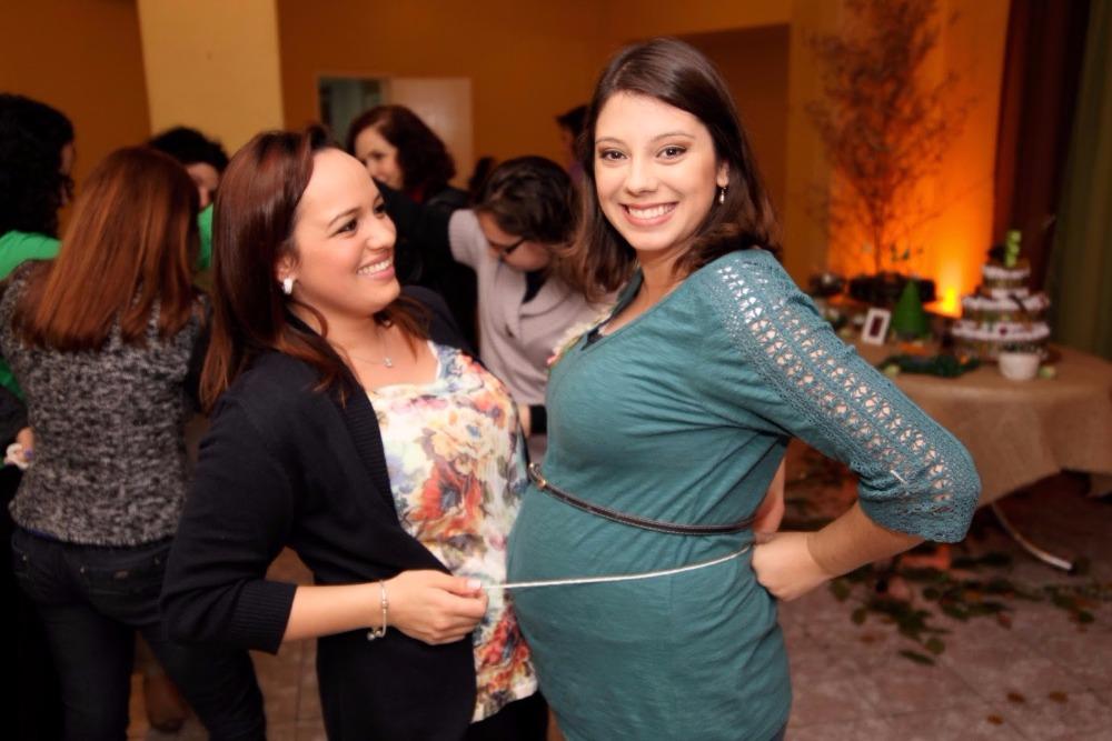 Amiga medindo a barriga da grávida com um barbante