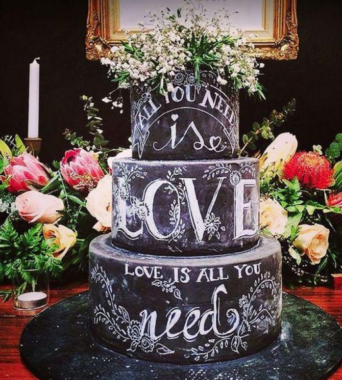 Bolo no estilo lousa faz parte da decoração da festa de casamento